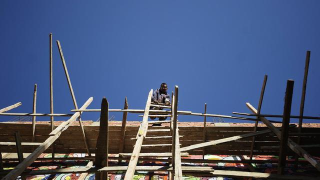 Diaa el-Sayyed, un jeune Egyptien, perché sur une échelle après avoir peint un mur, au Caire, le 19 janvier 2013 [Gianluigi Guercia / AFP]