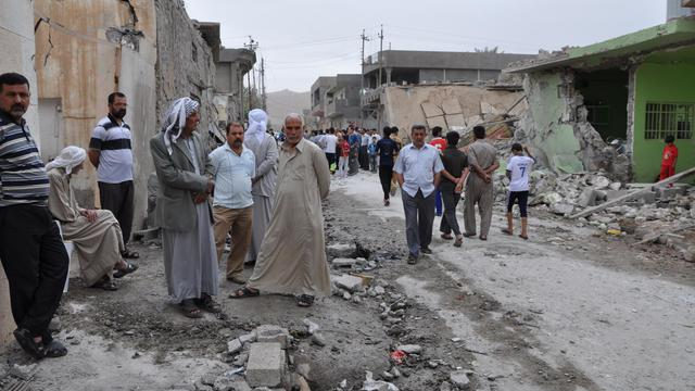 Des irakiens constatent les dégâts provoqués par deux attentats à la voiture piégée, le 21 mai 2013, dans la ville de Touz Khourmatou, au nord de Bagdad [Marwan Ibrahim / AFP]