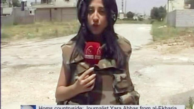 Capture d'écran du 27 mai 2013 montrant la journaliste Yara Abbas de la chaîne syrienne d'information en continu Al-Ikhbariya, alors qu'elle couvre le conflit [- / AFP]