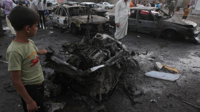 Des Irakiens sur les lieux de l'explosion de deux voitures piégées le 27 Mai 2013 à Bagdad [Ahmad al-Rubaye / AFP]