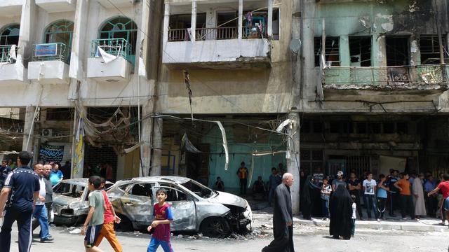 Des Irakiens passent le 28 mai 2013 à côté de véhicules et d'immeubles visés par un attentat la veille à Bagdad [Sabah Arar / AFP]