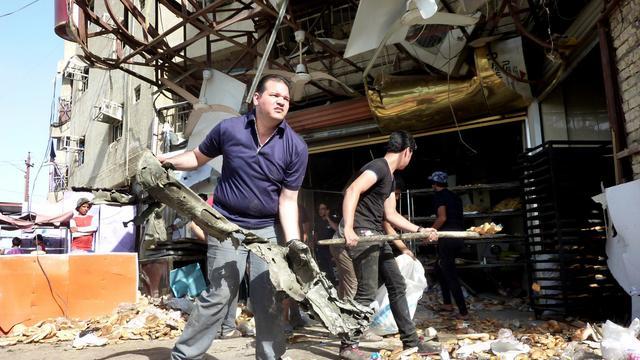 Des Irakiens nettoient les débris d'un attentat qui a fait 16 morts, le 28 mai 2013 à Sadr City à Bagdad [Ali al-Saadi / AFP]