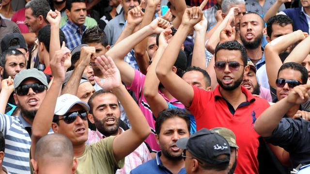 Des Tunisiens protestent à l'extérieur d'un tribunal où est jugée une Femen tunisienne, le 30 mai 2013 à Kairouan [Salah Habibi / AFP/Archives]