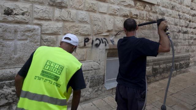 Un agent municipal efface un graffiti anti-chrétien en hébreu peint sur un mur de l'église de la Dormition, le 31 mai 2013 à Jérusalem [Ahmad Gharabli / AFP]