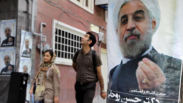 Des Iraniens marchent à côté de l'affiche de campagne du candidat Hassan Rowhani, le 1er juin 2013 à Téhéran [Atta Kenare / AFP]