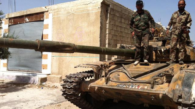 De soldats syriens sur un tank dans un village au nord de Qousseir, le 7 juin 2013 [ / AFP]