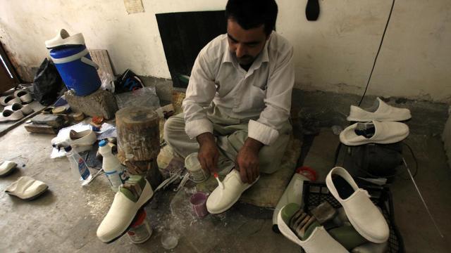 "Un Kurde dans son atelier de fabrication de ""klash"", la traditionnelle espadrille kurde, à Halabja, au Kurdistan irakien, le 16 mars 2013 [Ali al-Saadi / AFP]"