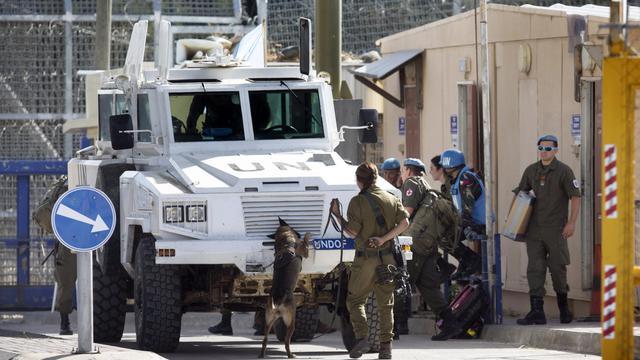 Un véhicule des Casques bleus autrichiens contrôlé le 12 juin 2013 au passage de Qouneitra par des soldats israéliens [Menahem Kahana / AFP]