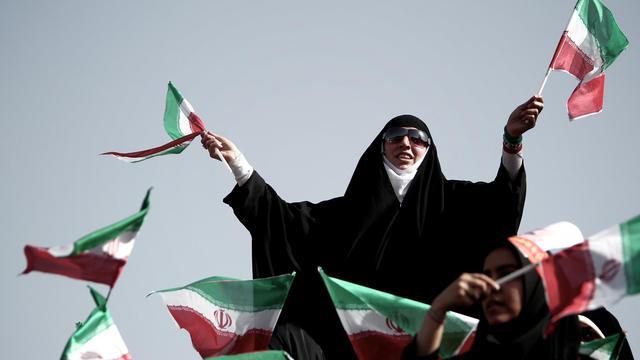 Des partisans du candidat à la présidentielle iranienne Saïd Jalil, chef des négociateurs nucléaires, brandissent le drapeau national lors d'un meeting à Téhéran le 12 juin 2013 [Behrouz Mehri / AFP]