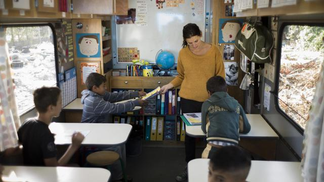 """""""Bonjour, on vient chercher les enfants pour l'école!"""". C'est la rentrée jeudi au bidonville de La Courneuve où vivent un millier de Roms. Trois enseignants font classe dans des camions colorés, dans l'espoir d'inscrire un jour les élèves dans une école en dur. [AFP]"""