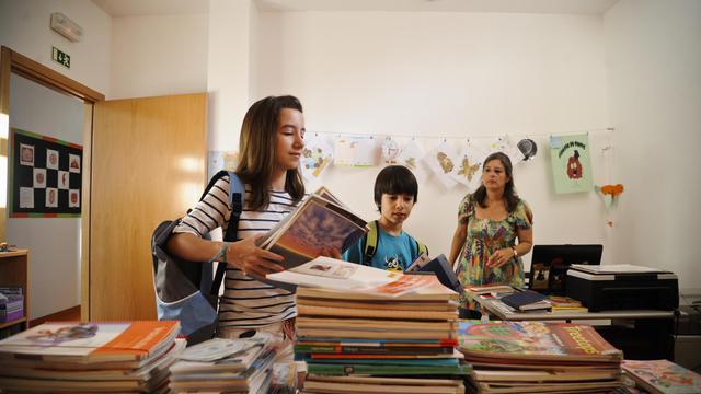 Des enfants déposent des livres d'occasion dans l'arrière boutique d'une supérette de Lisbonne, le 6 septembre 2012 [Patricia de Melo Moreira / AFP]