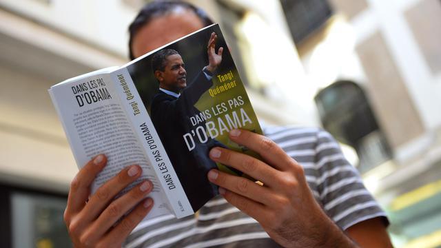 """Un homme lit """"Dans les pas d'Obama"""" (JC Lattès) de Tangi Quéméner le 13 septembre 2012 à Paris [Miguel Medina / AFP]"""