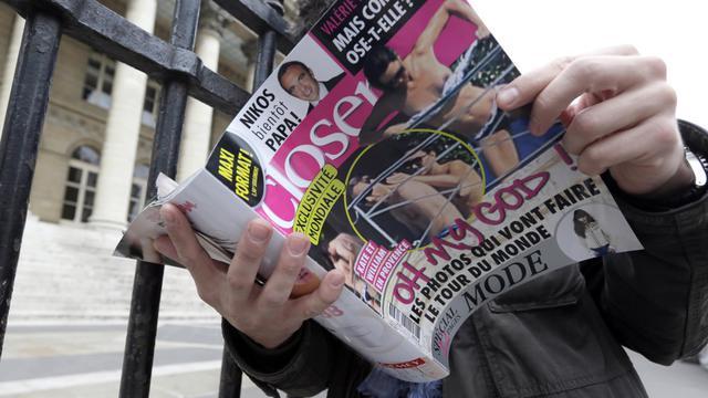 Un homme lit le magazine Closer montrant les seins nus de Kate Middleton, le 14 septembre 2012 [Kenzo Tribouillard / AFP]