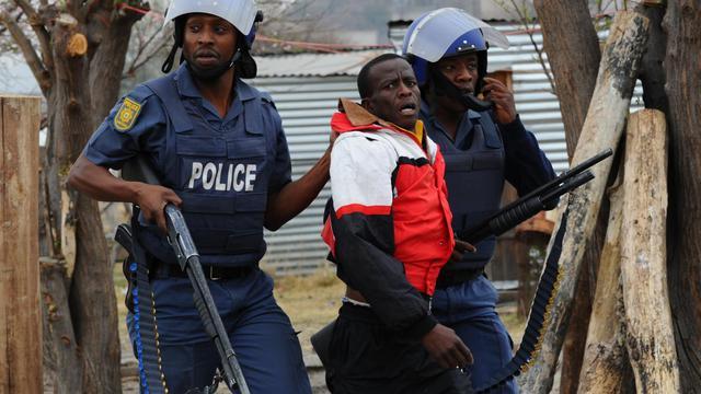 Des policiers sud-africains arrêtent un mineur à Marikana, le 15 septembre 2012 [Alexander Joe / AFP]