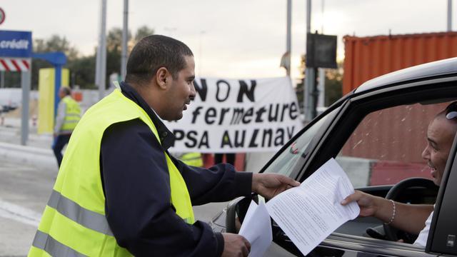 Un salarié de l'usine PSA d'Aulnay-sous-Bois distribue un tract à un automobiliste au péage de Senlis, le 16 septembre 2012 [Kenzo Tribouillard / AFP]