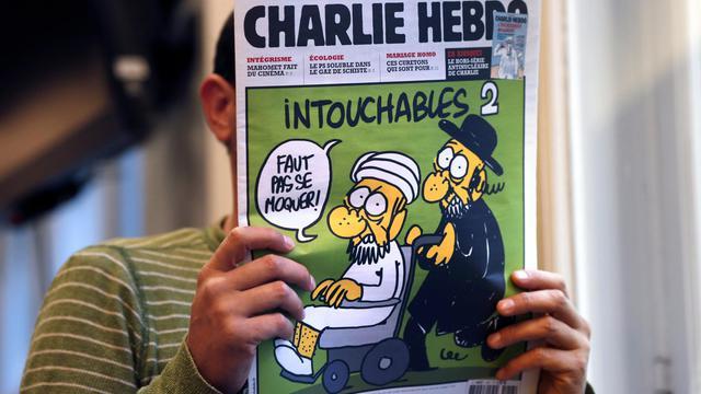 Un homme lit le numéro de Charlie Hedbo montrant des caricatures de Mahomet, le 19 septembre 2012 à Paris [Thomas Coex / AFP]