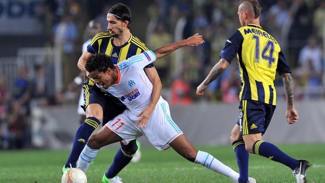 Le Marseillais Loïc Rémy (en blanc) à la lutte avec Hasan Ali Kaldirim (g), de Fenerbahçe en Europa League, à Istanbul, le 20 septembre 2012. [Bulent Kilic / AFP]