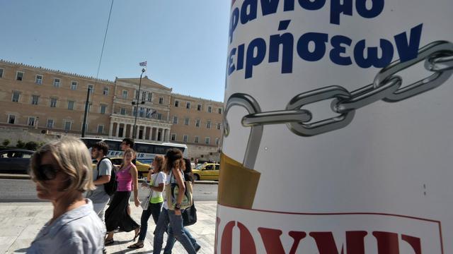 Des personnes passent devant le Parlement à Athènes et des affiches appelant à une grève générale, le 25 septembre 2012 [Louisa Gouliamaki / AFP]