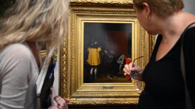 """Des personnes regardent le tableau de Jean Auguste Dominique Ingres """"L'Arétin et l'envoyé de Charles Quint"""", le 26 septembre 2012 à Lyon [Philippe Desmazes / AFP]"""