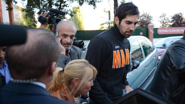 Le handballeur de Montpellier Nikola Karabatic (d) monte à bord d'une voiture de police après le match face au PSG, près de la salle Coubertin à Paris, le 30 septembre 2012. [Franck Fife / AFP]