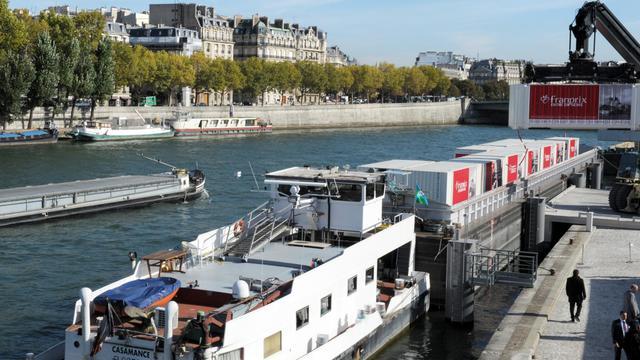 Des containers de marchandises destinés à des magasins Franprix sont chargés sur une péniche à Paris, le 1er octobre 2012 [Eric Piermont / AFP]