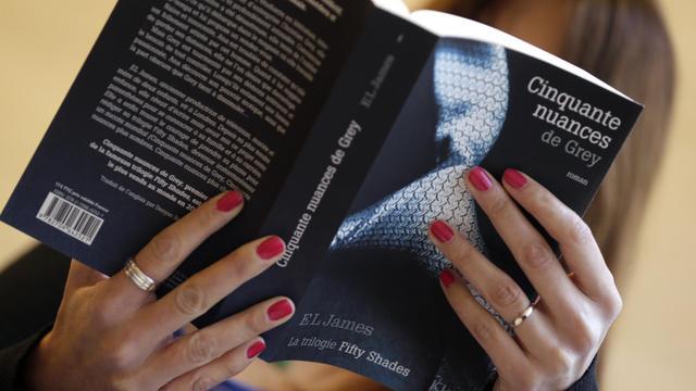 """Une femme lit le roman """"Cinquante nuances de Grey"""" le 16 octobre 2012 à Paris [Kenzo Tribouillard / AFP]"""