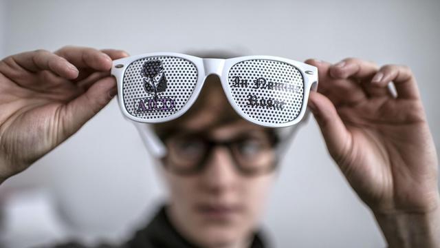 Un employé de Lulu Frenchie examine une paire de lunettes aux verres  décorés d une bb4fb94c0986