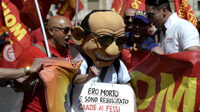 Un homme porte un masque géant de Berlusconi lors d'une manifestation à l'appel du syndicat italien des métallos Fiom, le 18 mai 2013 à Rome [Filippo Monteforte / AFP]