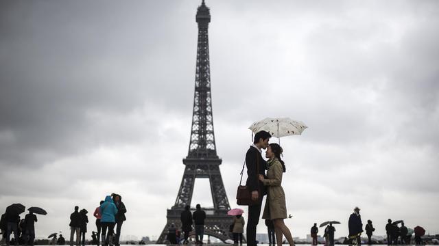 Des badauds sous la pluie, au Trocadéro, à Paris, le 20 mai 2013 [Fred Dufour / AFP]