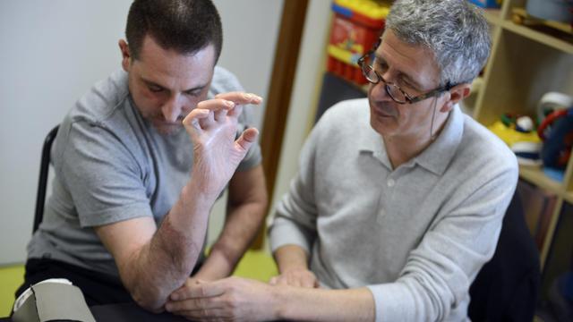 Aram Gazarian, spécialiste de la greffe des mains, examine le 22 mai 2013 à Miribel Stefano Sileoni (g), opéré en 2012 [Philippe Desmazes / AFP]