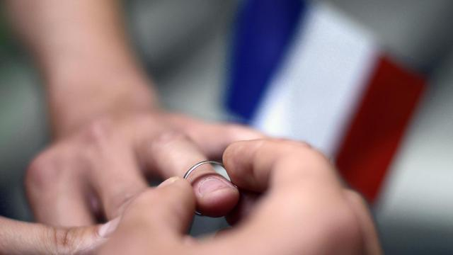 Deux personnes échangent des alliances [Kenzo Tribouillard / AFP/Archives]