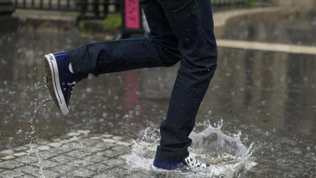Un piéton saute dans une flaque d'eau, le 30 mai 2013 à Paris [Fred Dufour / AFP]