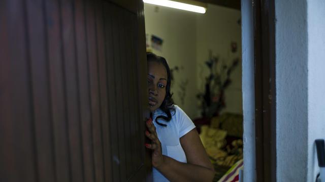 Mme Kouyaté ouvre la porte de sa cabane, le 1er juin 2013 à Stains en banlieue parisienne [Fred Dufour / AFP]