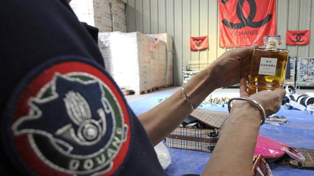 Un douanier montre un parfum de contrefaçon, à Marseille, le 11 juin 2013 [Boris Horvat / AFP]
