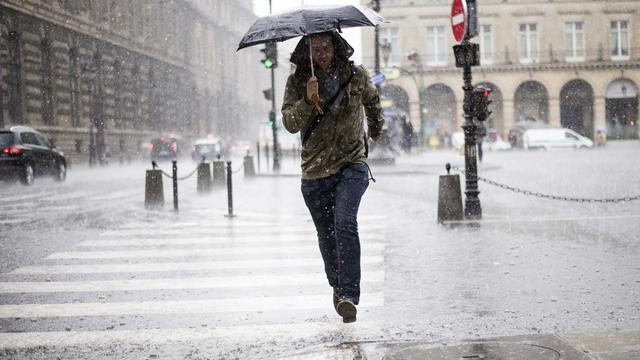 Une personne sous un orage le 17 juin 2013 à Paris [Fred Dufour / AFP]