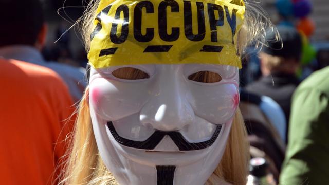 Une femme porte un masque d'Anonymous, le 17 septembre 2012, pour le premier anniversaire du mouvement Occupy Wall Street, à New York [Stan Honda / AFP]