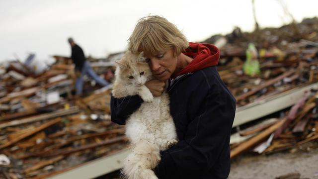 Une femme et son chat le 21 mai 2013 au milieu des décombres à  à Moore, une banlieue d'Oklahoma City dévastée par une tornade [Joshua Lott / AFP]