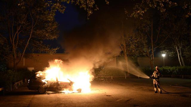 Un pompier éteint une voiture incendiée dans la banlieue de Stockholm, le 21 mai 2013 [Jonathan Nackstrand / AFP]