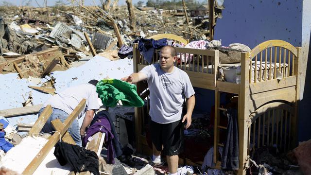 Des habitants de Moore le 22 mai 2013 au milieu des décombres de leurs maisons détruites [Joshua Lott / AFP]