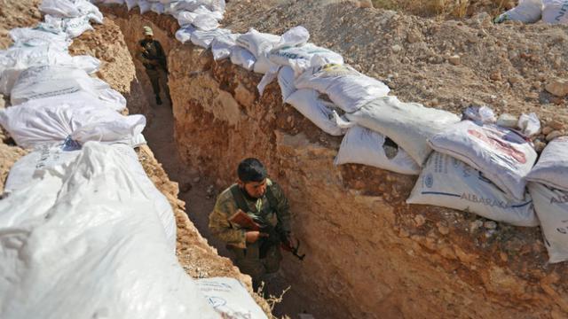 Un combattant du Front national de libération (FNL), principale coalition rebelle dans la province d'Idleb, dans le nord-ouest de la Syrie, marche dans une tranchée dans cette région le 31 août 2018 [OMAR HAJ KADOUR / AFP]
