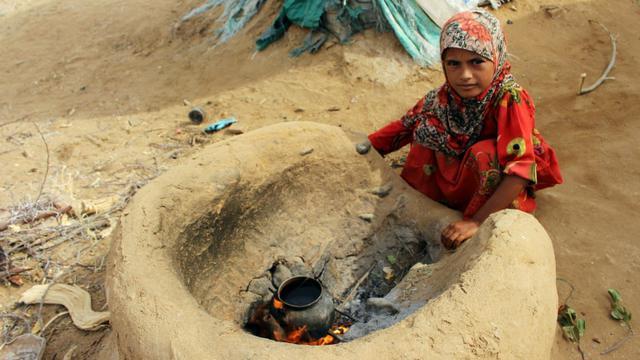 Une petite fille yéménite qui a fui la guerre dans la région de Harad, fait bouillir de l'eau dans un camp de déplacés à Abs dans la province de Hajjah, le 23 juillet 2017  [STRINGER / AFP/Archives]