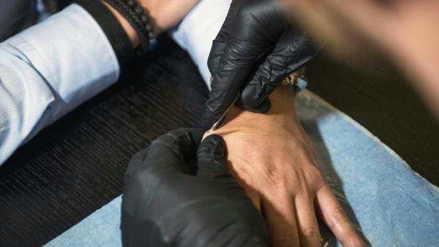 Un homme insère un implant électronique sous la peau d'un autre à l'aide d'une seringue, à Stockholm, le 18 janvier 2018 [Jonathan NACKSTRAND / AFP]