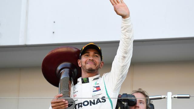 Le Britannique Lewis Hamilton salue sur le podium les supporteurs après sa victoire au GP du Japon de F1, le 7 octobre 2018 sur le circuit de Suzuka [Toshifumi KITAMURA / AFP]