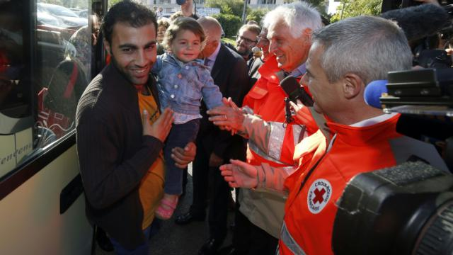 Des membres de la Croix-Rouge, dont son président Jean-Jacques Eledjam (2e à d.), accueillent des migrants arrivant d'Allemagne, le 9 septembre 2015 à Champagne-sur-Seine (Seine-et-Marne) [PIERRE CONSTANT / AFP]