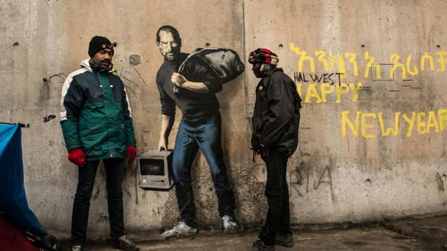 """Des migrants devant une oeuvre de l'artiste britannique Bansky photographiée le 12 décembre 2015 et située à l'entrée de la """"Jungle"""" de Calais, représente Steve Jobs (Apple), qui porte un baluchon et un vieil ordinateur [PHILIPPE HUGUEN / AFP]"""