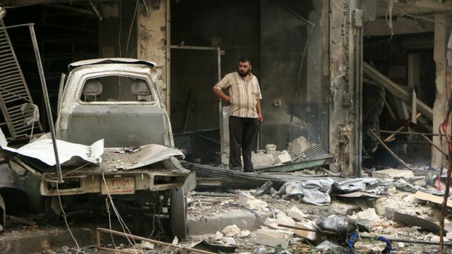 Un Syrien au milieu des ruines après des frappes de l'armée de l'air le 21 septembre 2015 à Alep [Fadi al-Halabi / AFP]
