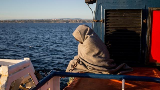 Un migrant enveloppé dans une couverture sur le pont du Sea-Watch peu avant l'arrivée du navire à Catane (Sicile), le 31 janvier 2019 [FEDERICO SCOPPA / AFP]