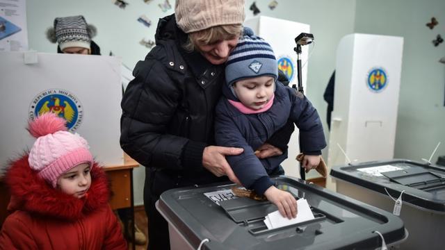 Une femme dépose son bulletin dans l'urne à  Chisnau le 24 février 2019, jour de l'élection des députés moldaves [Daniel MIHAILESCU / AFP]