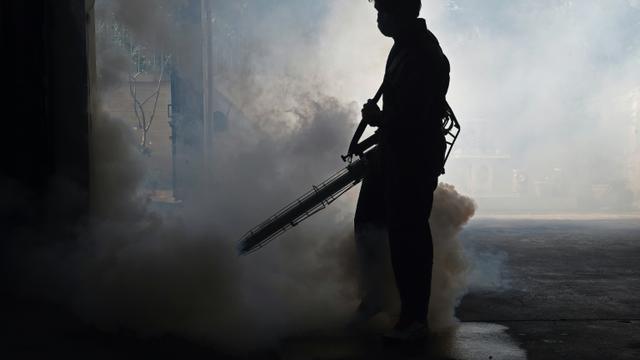 Un employé municipal fumige une maison pour lutter contre le moustique Aedes Aegypti, vecteur du virus Zika et celui de la dengue, le 5 février 2016 à Bangkok [CHRISTOPHE ARCHAMBAULT / AFP]