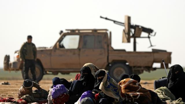 Des civils ayant fui les combats contre le groupe Etat islamique (EI) dans son ultime réduit de Syrie, et derrière eux un combattant des Forces démocratiques syriennes (SDF), près du village de Baghouz, le 3 février 2019 [Delil souleiman / AFP/Archives]